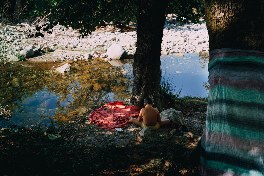 A boy sitting among the trees near the river at a canyon, shot at Samothraki, Greece on August of 2016, image by Ilias Antoniou.