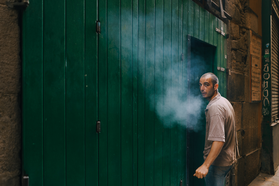 Smoking man entering green door in an alley in Barcelona, photography by Ilias Antoniou