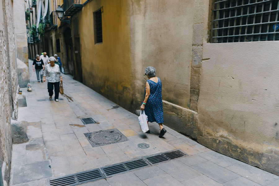 Old woman walking by an alley in Barcelona, photography by Ilias Antoniou