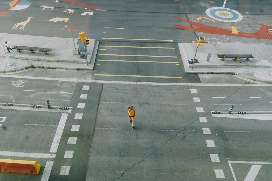 Yellow dressed girl crossing a street with yellow details, viewed from a window at the Design Museum of Barcelona, photography by Ilias Antoniou