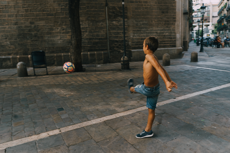 Children kicking a football towards an old wall, photography by Ilias Antoniou
