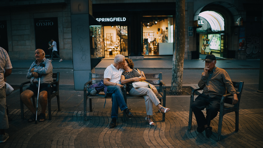 Old couple kissing at a bench in Barcelona, Spain, photography by Ilias Antoniou